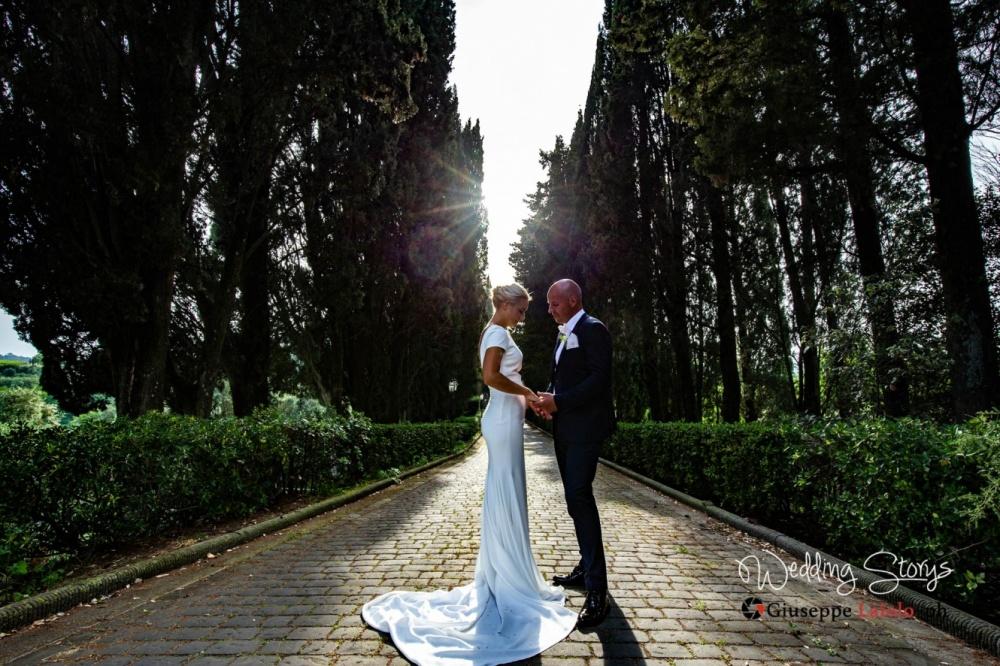 particolare degli sposi nel viale alberato che porta alla villa storica per matrimonio