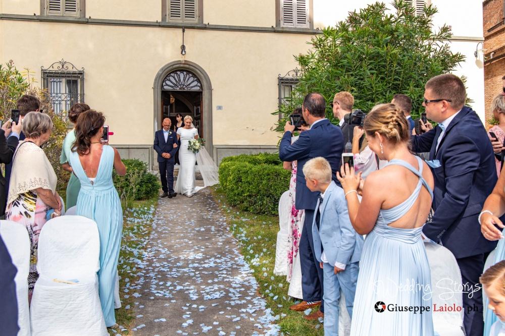 il padre della sposa la accompagna verso lo sposo nell'esterno della location esclusica per nozze