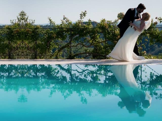 sposa e sposo in un antico borgo con piscina per sposarsi in una villa Toscana